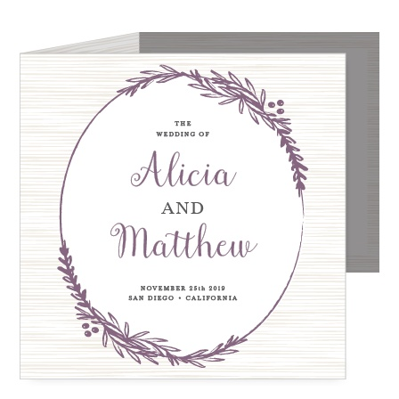 A subtle wood grain background and a frame of foliage decorate the front of the Delicate Laurel Storybook Wedding Invitations.